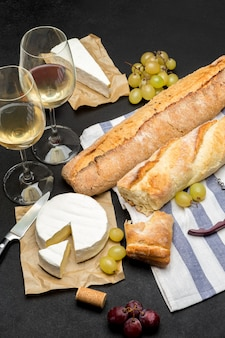 Brie cheese, baguette and two glasses of white wine on dark concrete background