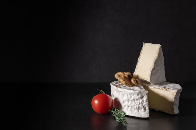 Сыр бри. сыр типа бри с грецкими орехами и помидорами. камамбер. свежий сыр бри и кусочек на каменной доске.
