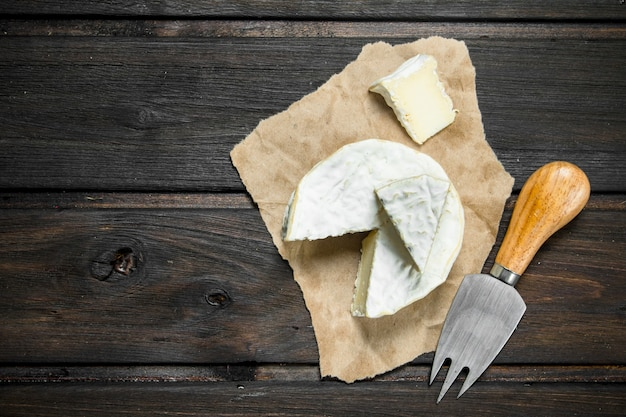 Brie cheese on old paper on wooden table.