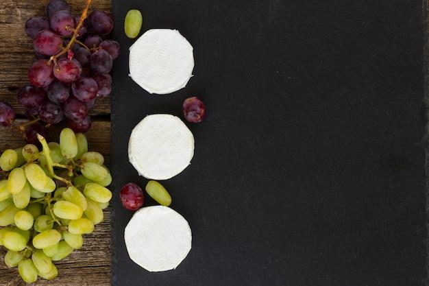 Сыр бри на черной разделочной доске с красным и белым виноградом, копией пространства