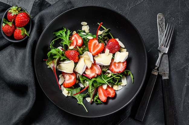 Brie cheese salad with strawberries, nuts, chard and arugula. black background. top view.