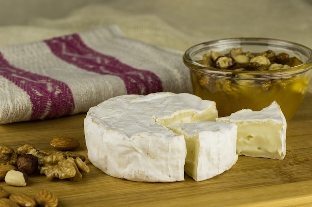 Brie cheese and a slice on a wooden board with nuts