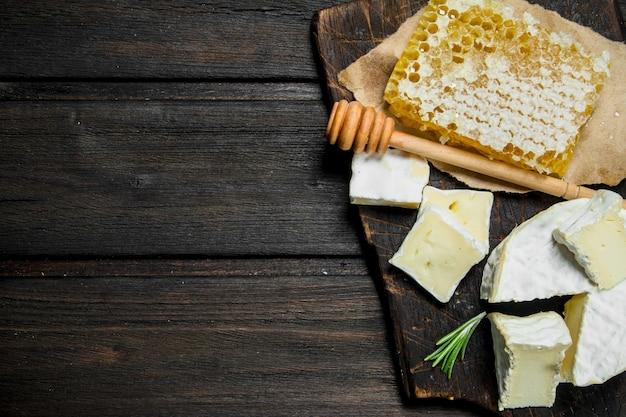 木製のテーブルに蜂蜜の櫛とブリーチーズ。