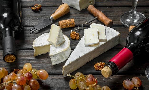 木製のテーブルに赤ワイン、ナッツ、ブドウとブリーチーズ。