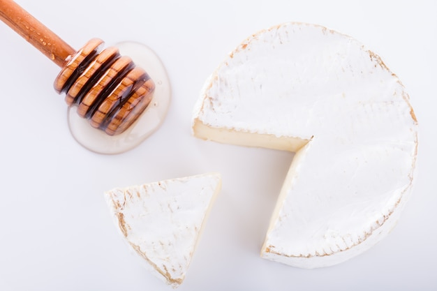 Brie cheese on with a white background with fresh ingram and honey
