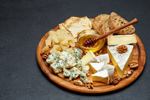 Brie cheese on a wooden board with bread and sweet honey