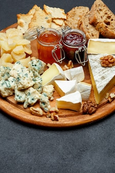 Brie cheese on a wooden board with bread and sweet jam