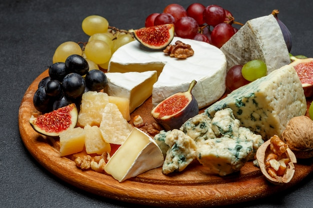 Brie cheese on a wooden board with fresh figs and grapes