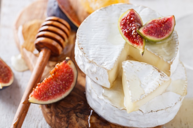 Brie cheese on a wooden board with fresh figs and honey