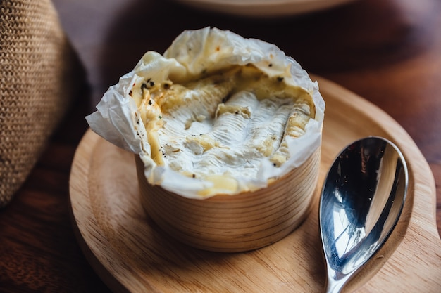Brie cheese on wooden board.
