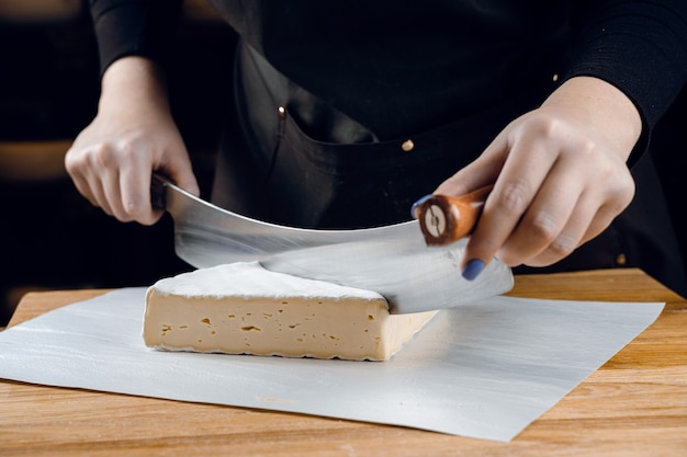 Brie soft white cheese from cow milk. slicing brie on the wooden table. organic delicious food.