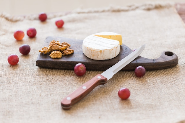Brie type of cheese. camembert cheese. fresh brie cheese on a wooden board with nuts and grapes