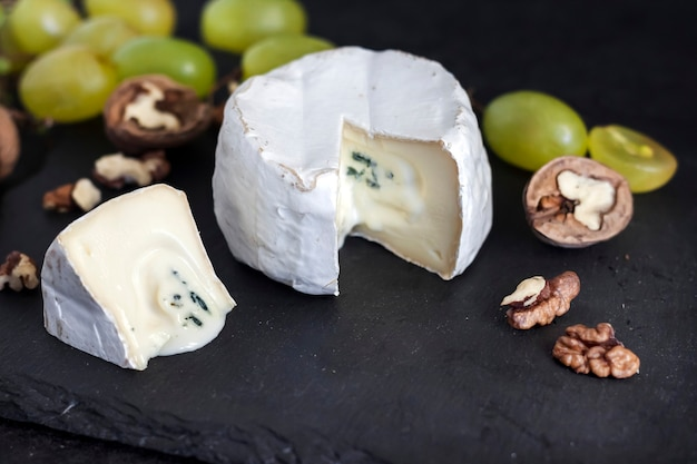 Brie type of cheese. soft cheese with grapes and walnuts on black background