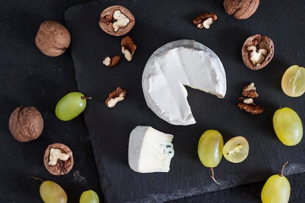 ブリーチーズタイプ。黒の背景にブドウとクルミの柔らかいチーズ。フラットレイ、上面図