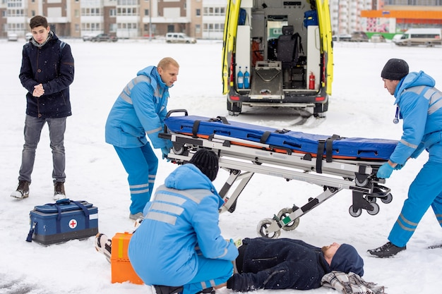Brigade of young paramedics in workwear preparing stretcher for sick unconscious man lying in snow