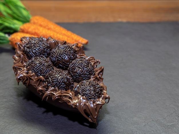 Шоколадное пасхальное яйцо brigadeiro на черном каменном фоне с копией пространства