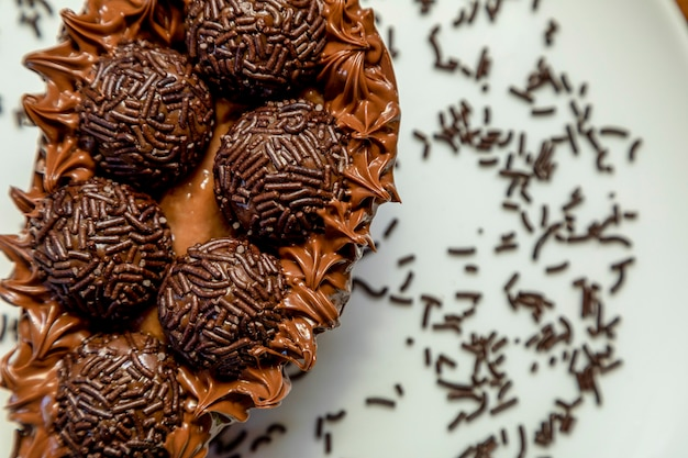 Шоколадное пасхальное яйцо brigadeiro на фоне белой тарелки