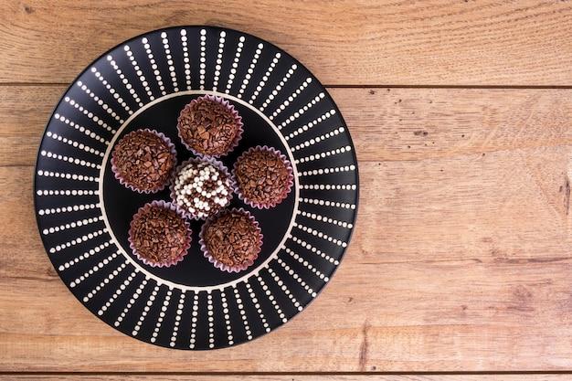 Бригадиры в черном блюде на деревянном столе - вид сверху