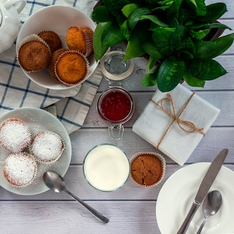 Bright and airy breakfast with muffin, berry jam and milk in glass.