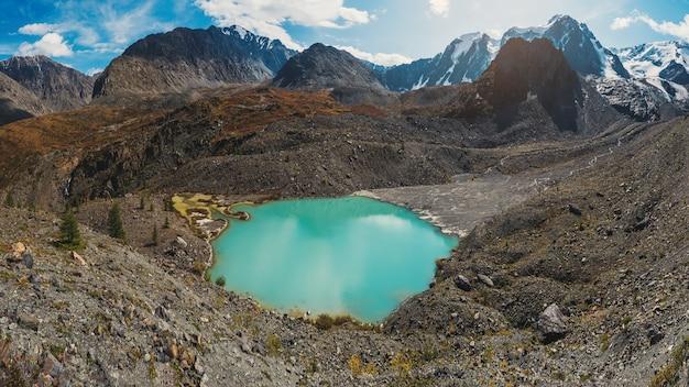 日光の下で高原の谷の山の湖と青い曇り空の下の大きな山と明るい高山の風景。秋の山の谷の雲の影。パノラマビュー。