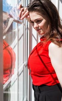 Яркая и модная брюнетка в красной кофточке смотрит в окно. за окном солнечная погода, на девушку падает тень из окна.