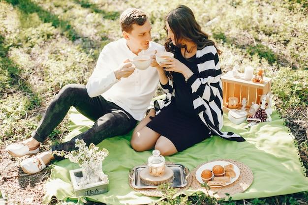 Яркая и счастливая беременная женщина, сидящая в парке с мужем и пить чай