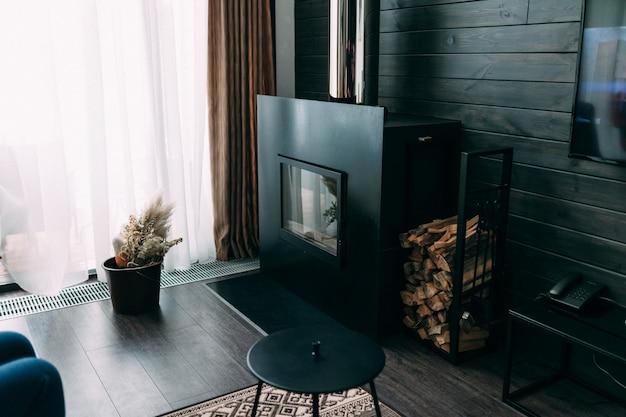 暖炉、大きなソファ、小さなテーブル、パターンの壁紙を備えた明るく広々とした豪華なリビングルーム。ロフトと素朴なスタイル