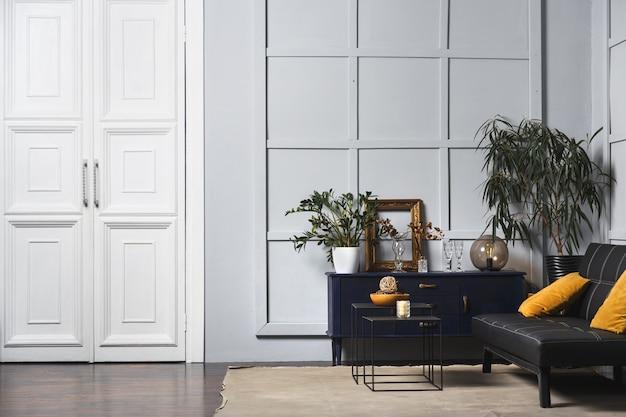 黒革のソファ、装飾された壁のランプとテーブルを備えた明るいアパートのインテリア。