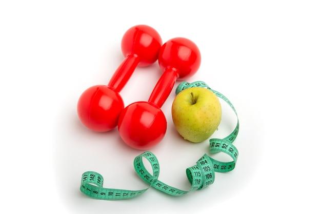 Яркое яблоко и красные гантели с измерительной лентой на белом изолированном