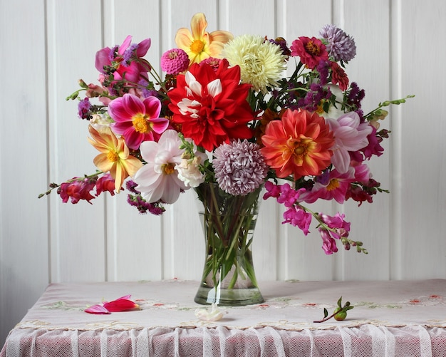 유리 꽃병에 흰색 벽 소박한 인테리어 꽃 근처 테이블에 달리아와 애스터의 밝은 가을 꽃다발