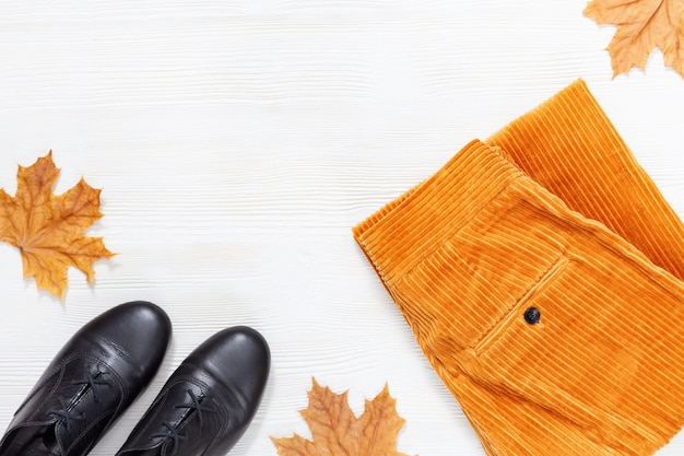 Bright autumn flat lay with black boots and fashion orange corduroy trousers