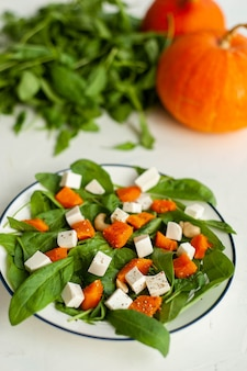 Bright autumn salad of spinach and pumpkin with feta cheese. healthy food. high quality photo
