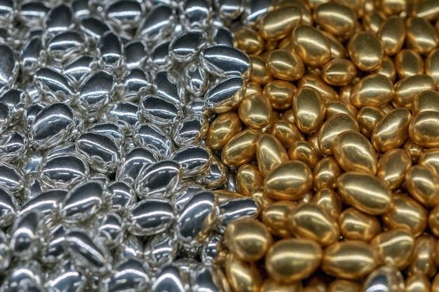 金と銀の甘いキャンディーで作られた明るい背景。