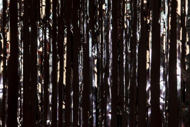 어두운 벽에 금속 호일로 만든 반짝이의 밝은 배경