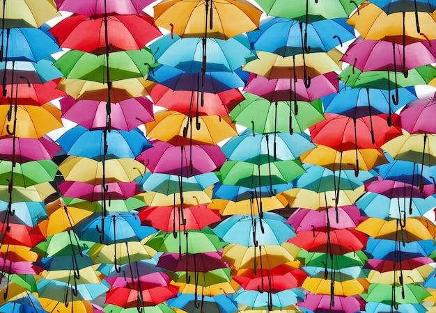 さまざまな色の開いた傘と明るい背景
