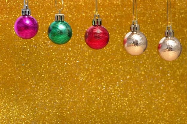 明るいボールが光沢のあるライトゴールドの背景にぶら下がっています。コピースペースとクリスマスの背景。背景がぼやけている/黄色の背景に円形のライト。