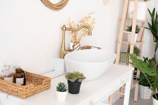 Яркая ванная, раковина, смеситель, зеркало, плетеная корзина и цветы на белом шкафу.