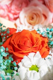バラの赤、黄、ピンクの明るく美しい花束がクローズアップ Premium写真