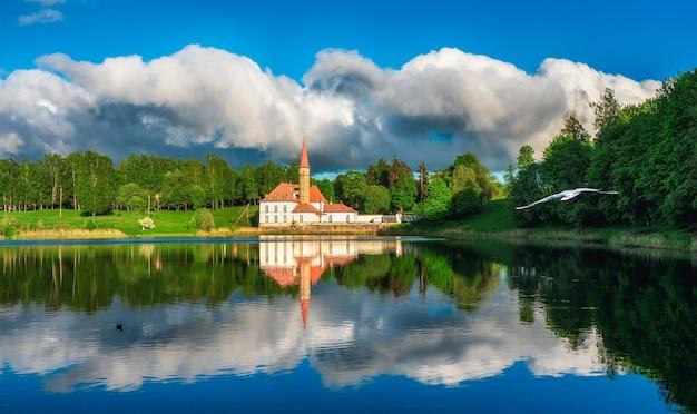 穏やかな湖、劇的な空、古い白いマルタの城のある明るく美しいパノラマの春の風景。ガッチナ。ロシア。