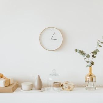 시계, 유칼립투스 지점, 꽃병, 촛불 밝은 베이지 색과 황금색 아파트.