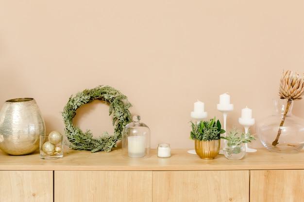 モミの枝の金のおもちゃで作られた花輪と明るいベージュと金色のアパート