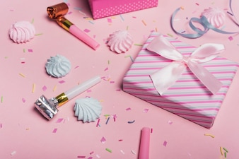 Bright birthday background with candies; party blowers and gift box