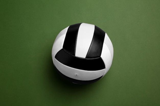 Bright black and white volleyball ball. professional sport equipment isolated on green studio background. concept of sport, activity, movement, healthy lifestyle, wellbeing. modern colors.
