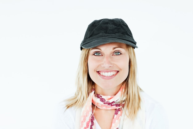 Bright blond woman with cap and scarf smiling at the camera against a white background