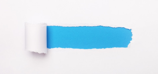 On a bright blue background, white paper with a torn stripe and a place to insert the text. template