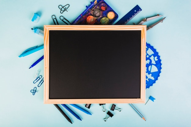 Bright blue drawing instruments around chalkboard