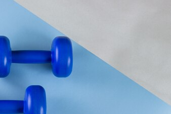 Bright blue dumbbells on a blue background. Cares about the body. Empty place for text.