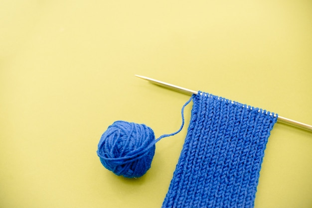 Bright blue  knitted  scarf with knitting needles light yellow background