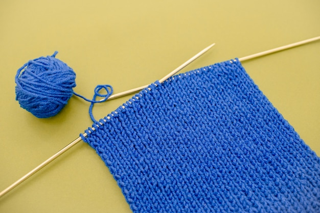 Bright blue  knitted  scarf with knitting needles
