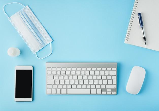Bright blue modern desk with medicine mask and sanitizer. t